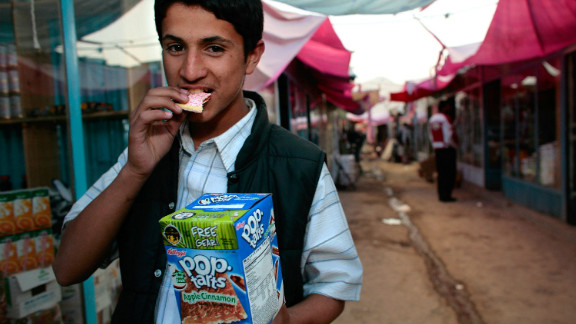 An Afghan merchant takes a bite of a Pop-Tart outside at the Bush Market on October 29, 2006 in Kabul, Afghanistan. The small black market named after ex-U.S. President George W. Bush is flooded with cheap American goods coming from military surplus, as well as some stolen goods.