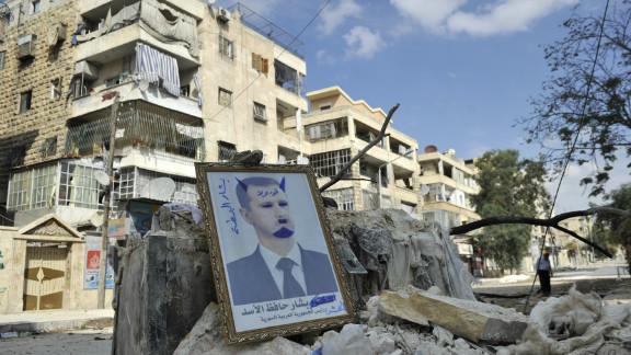 A portrait of Syrian President Bashar al-Assad sits on rubble along a street in the Saif al-Dawla district of Aleppo on Tuesday.