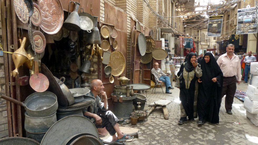 Iraqi women walk past vendors at the Safafir Market in Baghdad on April 4, 2012. Although violence is down in recent years, Meyer says kidnapping and assassinations are part of daily life in the capital.