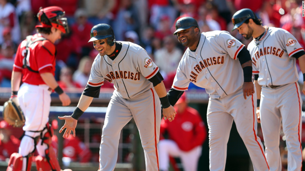 Teammates Marco Scutaro, Pablo Sandoval and Angel Pagan wait for Buster Posey at home plate after the Giants catcher hit a grand slam in the fifth inning off Cincinnati's Mat Latos.