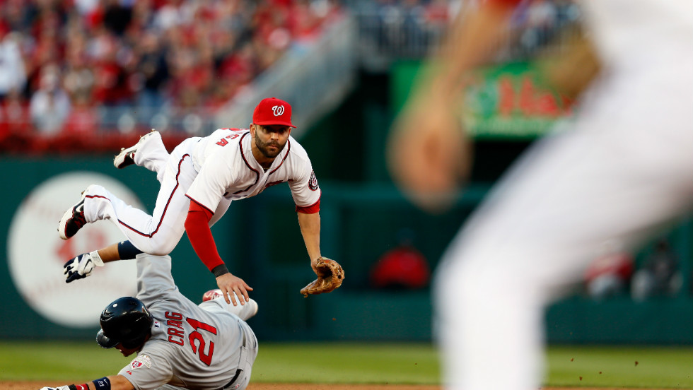 Allen Craig of the St. Louis Cardinals slides safely into second base as Danny Espinosa of the Washington Nationals throws to first to retire the Cards' Yadier Molina in the top of the sixth inning in Washington.