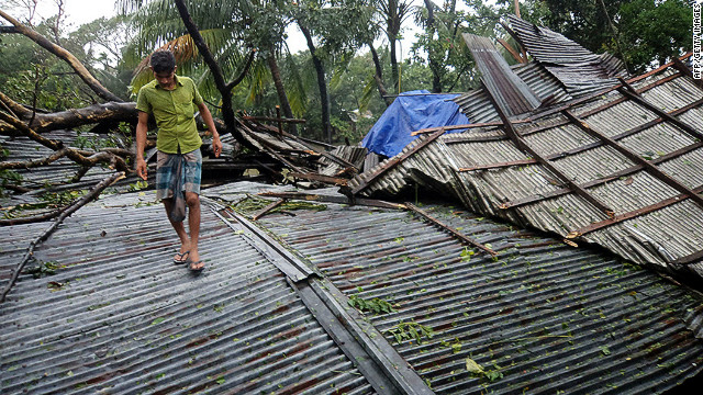 A Bangladeshi resident walks over the destroyed roof of a building on Bhola island on Thursday.
