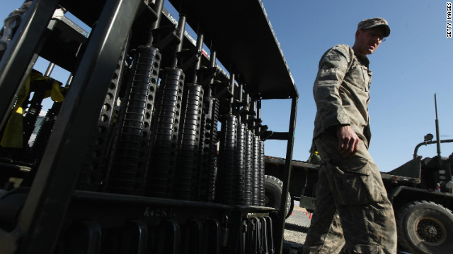 A U.S. Army soldier walks past weapons that arrived in the last U.S. military convoy to depart Iraq on December 18 in Kuwait.