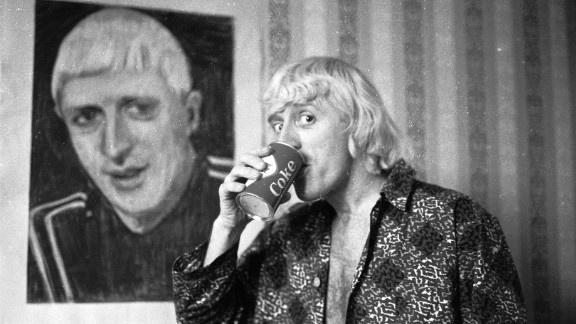 "The first presenter of long-running music program ""Top of the Pops,"" Savile poses by a portrait of himself in February 1965, while enjoying his regular breakfast of Coke and a cigar in a central London hotel room."