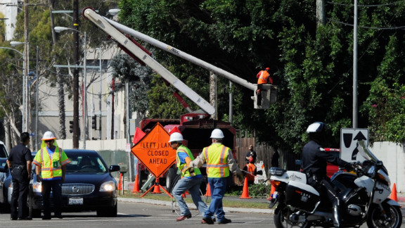 Tree trimmers cut large branches of a tree that was protruding toward the street in a last-minute effort to clear hurdles along the space shuttle Endeavour's route on Friday.