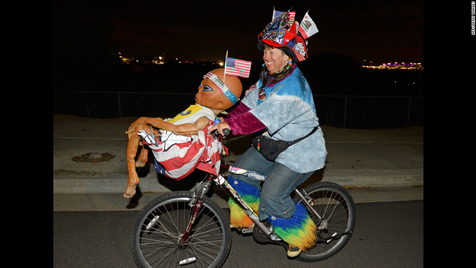 Fan Vivian Robinson rides her bicycle covered in shuttle memorabilia, American flags and an alien doll outside the Los Angeles airport as she waits to see Endeavour.