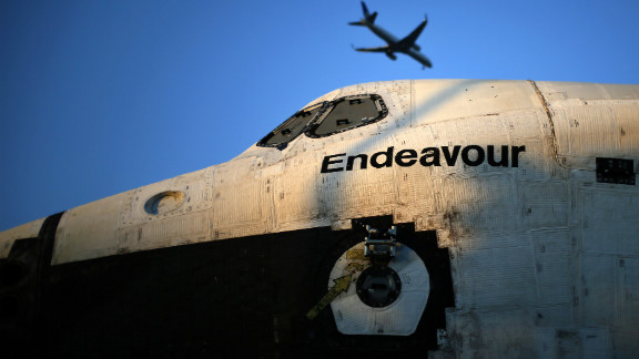A plane flies over the space shuttle Endeavour as it is moved to the California Science Center on Saturday.