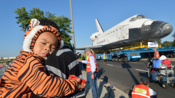 Mikael Ector, 2, tries to get some rest as his dad, Michael Ector, checks out Endeavour as it arrives at the Forum on Saturday.