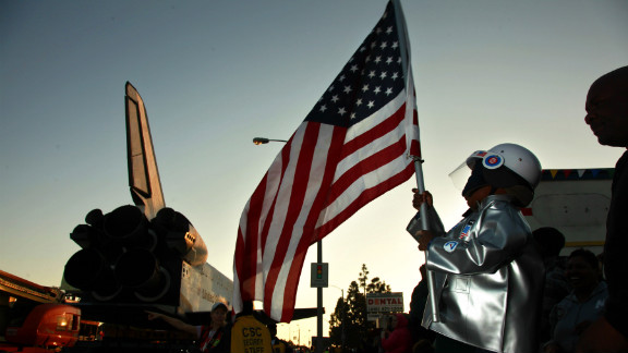 Amir Morris, 3, wears an astronaut costume while holding an American flag as the space shuttle crawls past.