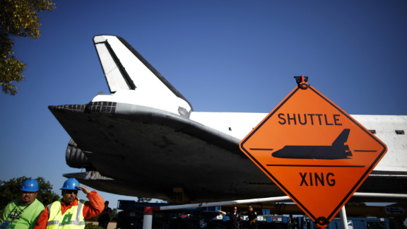 "The space shuttle Endeavour passes a ""Shuttle crossing"" sign on its way to the California Science Center on Saturday in Inglewood, California."