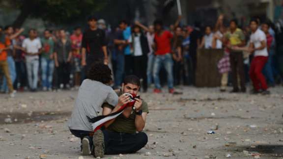 An anti-Muslim Brotherhood and President Mohamed Morsy protester cries on the ground as a man tries to calm him  during clashes with Morsy supporters in Tahrir Square in Cairo on Friday, October 12.