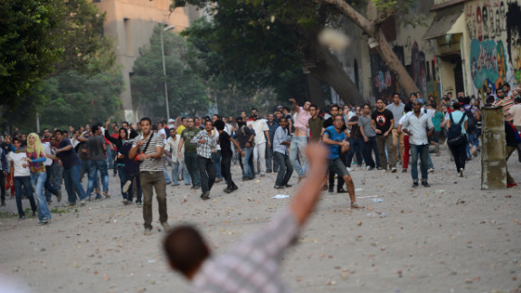 Protesters and government supporters throw stones at each other during clashes on Friday.