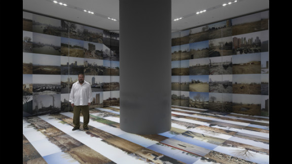 """Ai Weiwei poses in 2009 at the Mori Art Museum inTokyo with his work """"Provisional Landscape"""" (2002-2008). It"""