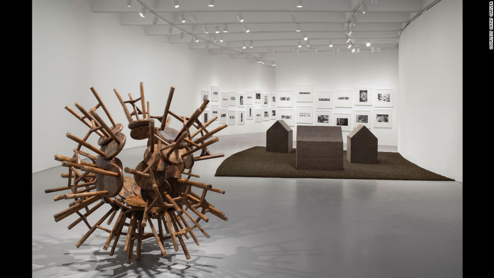 """Grapes"" (2010), left, transforms Qing Dynasty-era stools into a new vision. In the background are ""New York Photographs"" (1983-1993), which documents Ai's years in the downtown scene, and ""Tea House"" (2009)."