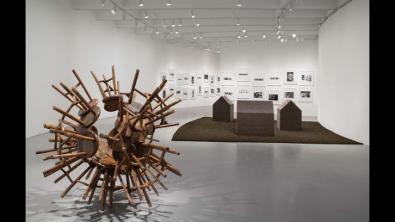 """""""Grapes"""" (2010), left, transforms Qing Dynasty-era stools into a new vision. In the background are """"New York Photographs"""" (1983-1993), which documents Ai's years in the downtown scene, and """"Tea House"""" (2009)."""