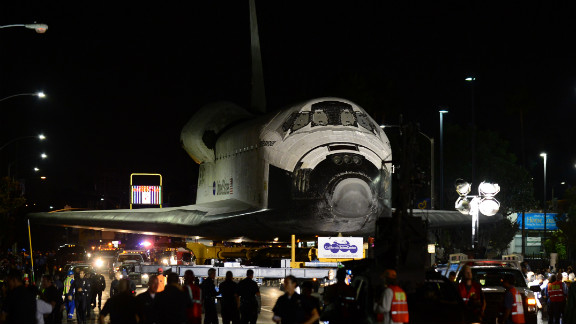 The space shuttle Endeavour makes its way down a city street under heavy escort on Saturday, October 13.