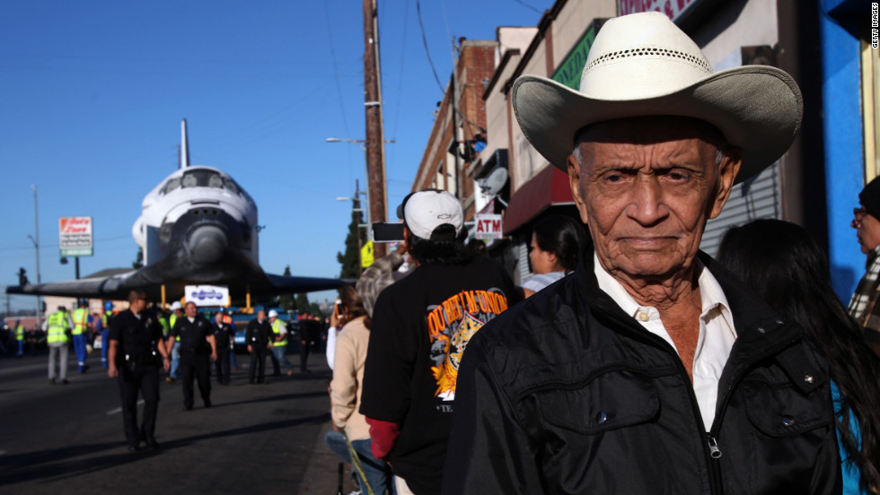 Federico Gonzales is among the many spectators as Endeavour inches down Martin Luther King Boulevard in Los Angeles on Sunday.