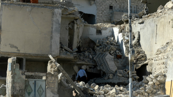A man inspects a destroyed building following shelling by regime forces in the northern city of Aleppo on Monday.
