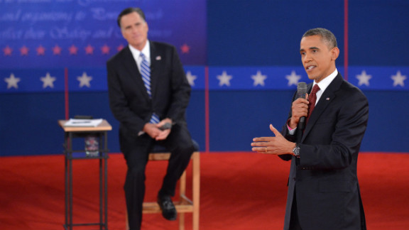 President Obama promotes his policies as Mitt Romney listens.