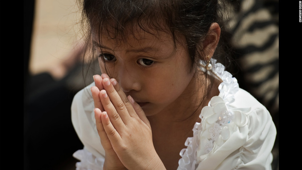 A Cambodian girl prays for the late former king in front of the Royal Palace in Phnom Penh on Wednesday.