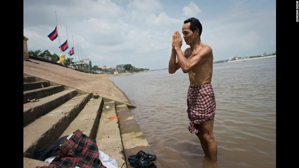 A Cambodian man makes a traditional gesture on Tuesday after he prayed over the death in the Tonle Sap River in Phnom Penh.