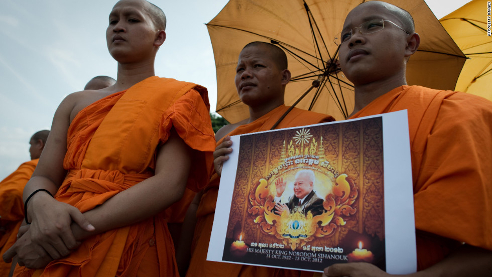 Buddhist monks hold a picture of late king as they wait for the convoy to go by with his coffin, in front of the Royal Palace in Phnom Penh.