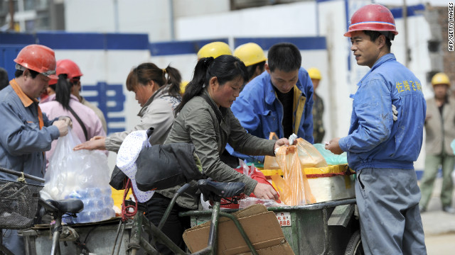 A worker (R) buys meal from a mobile vendor outside the construction site of a new real estate project in Beijing, April 12, 2012. A new World Bank report projects GDP growth in China will be 8.2 percent in 2012 and 8.6 percent in 2013. The China Quarterly Update, released April 12, says that the prospects for a gradual adjustment of growth remain high. AFP PHOTO / LIU JIN (Photo credit should read LIU JIN/AFP/Getty Images)