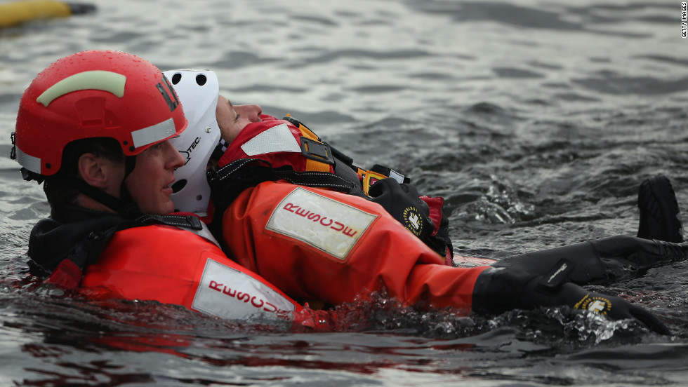 A firefighter carries a participant through the water during a demonstration.
