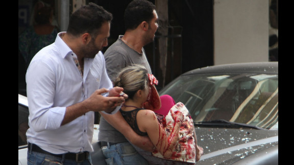 Lebanese men evacuate a wounded woman from the scene of the car bomb.