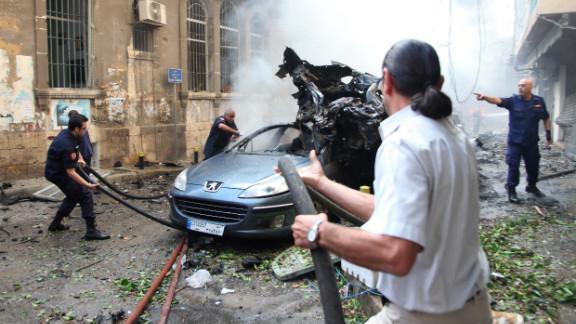 Lebanese firefighters douse burning vehicles.