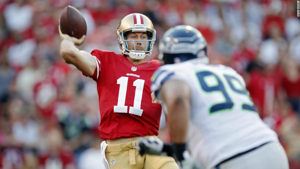Alex Smith of the San Francisco 49ers makes a pass under pressure from defensive tackle Alan Branch of the Seattle Seahawks during the first quarter.