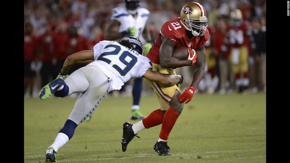 Runningback Frank Gore of the 49ers carries the ball for a 37-yard gain, breaking the tackle of Earl Thomas of the Seahawks, during the fourth quarter.