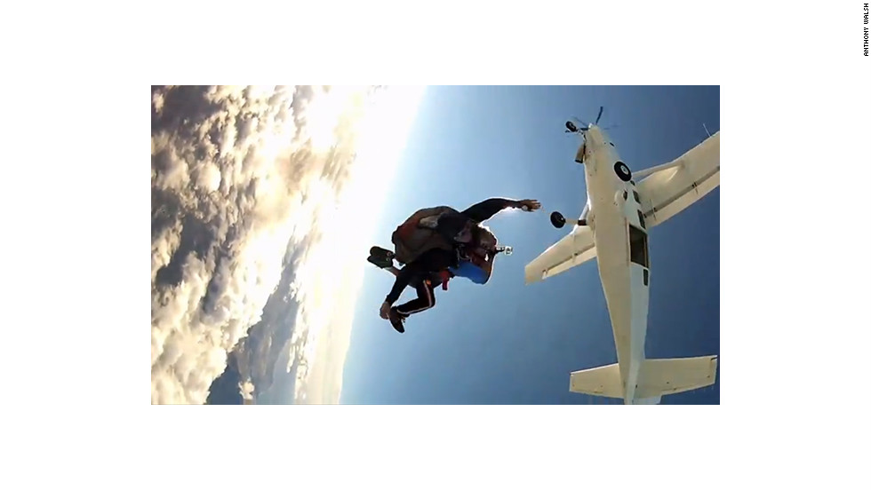 Tandem skydivers jumping out of a plane, each wearing mounted GoPro cameras, are captured by another jumper.