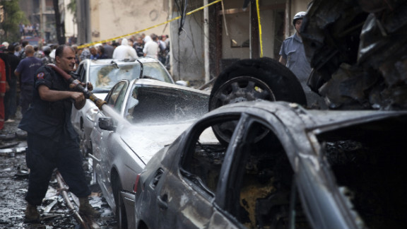 A Lebanese firefighter douses cars at the site of an explosion in Beirut