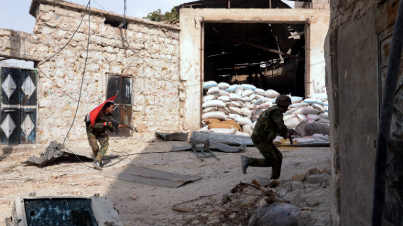 Syrian army soldiers run for cover during clashes with rebel fighters at Karam al-Jabal neighborhood of Aleppo on October 20, 2012.