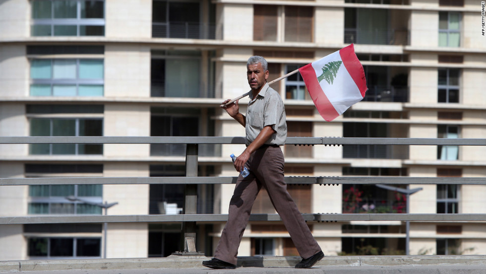 A Lebanese man holding the national flag watches the funeral procession on Sunday.