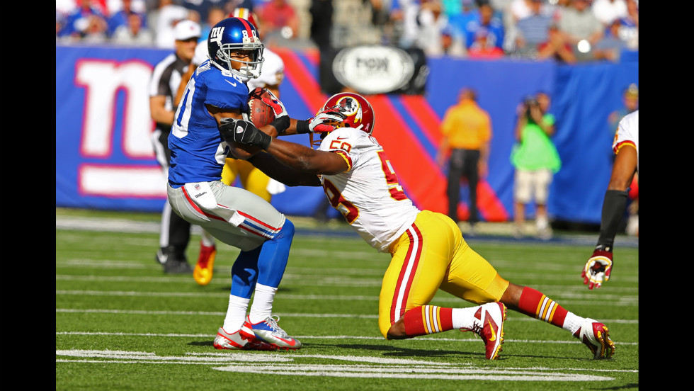 Victor Cruz of the Giants runs with the ball after a catch against  London Fletcher of the Redskins on Sunday.