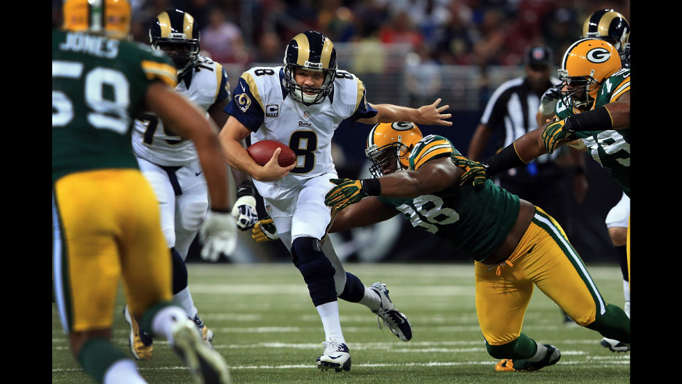Quarterback Sam Bradford of the Rams scrambles to elude C.J. Wilson of the Packers on Sunday.