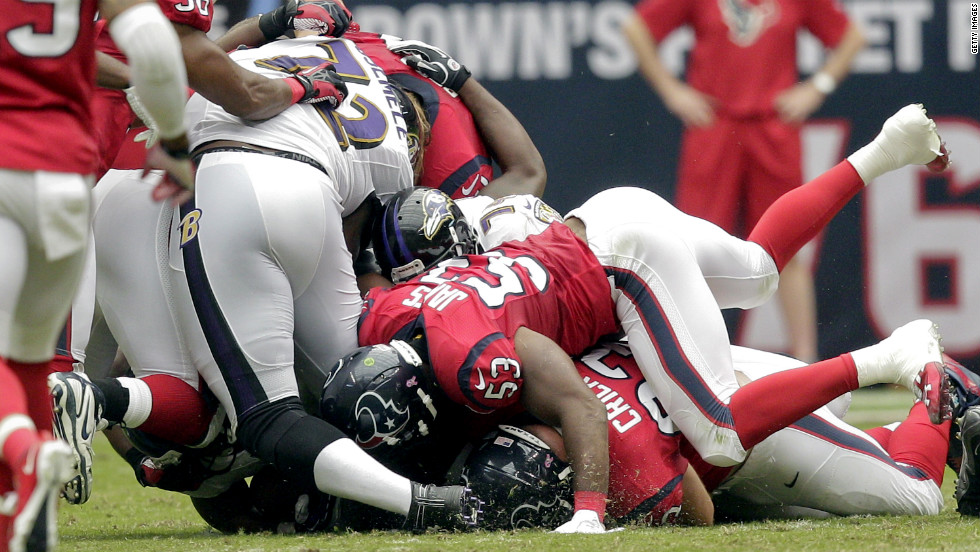 No. 72 Kelechi Osemele of the Baltimore Ravens has his leg pinned underneath him as No. 53 Bradie James of the Houston Texans falls on him Sunday at Reliant Stadium in Houston.