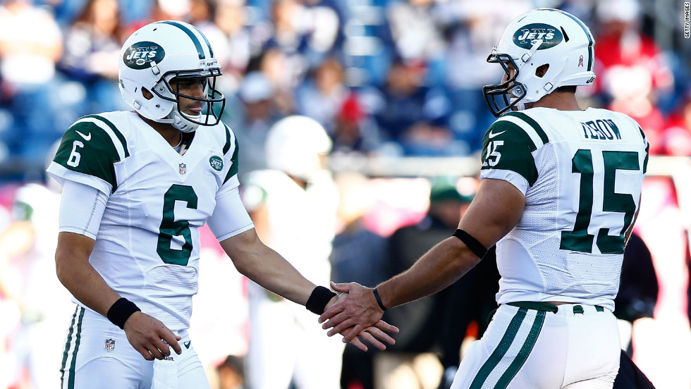 Jets quarterbacks Mark Sanchez and Tim Tebow greet each other during warm-ups before Sunday's game against the Patriots.