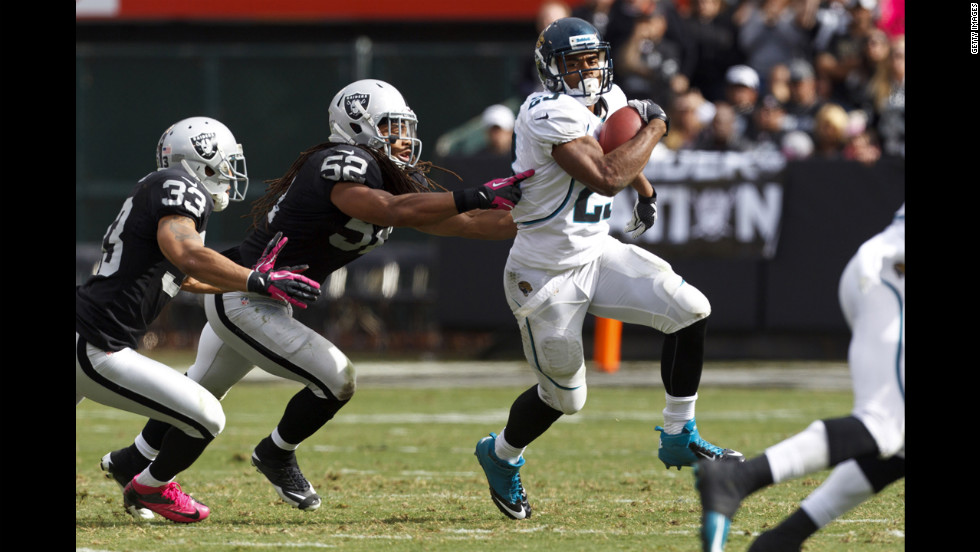 Rashad Jennings of the Jacksonville Jaguars rushes past Tyvon Branch, left, and Philip Wheeler of the Oakland Raiders.
