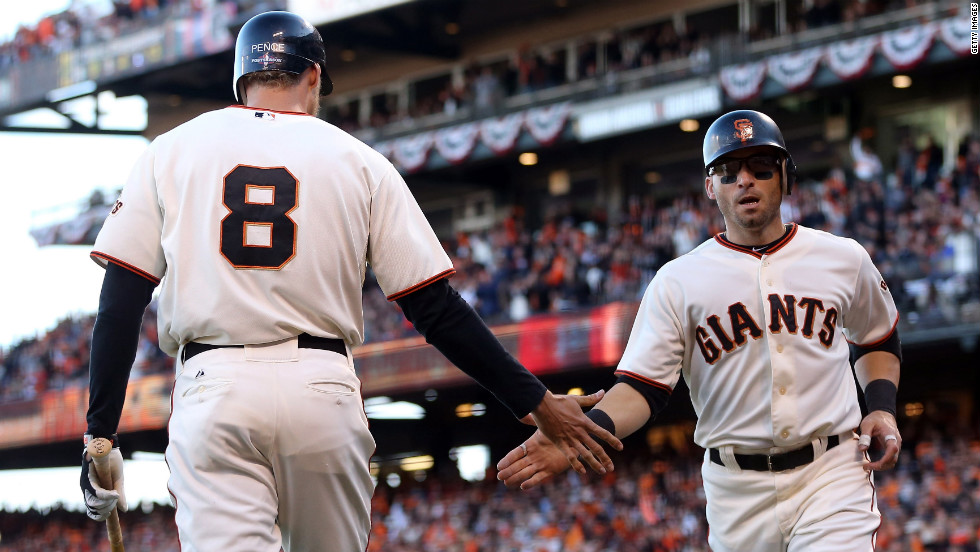 Marco Scutaro, right, is congratulated by Giants teammate Hunter Pence after scoring in the first inning.