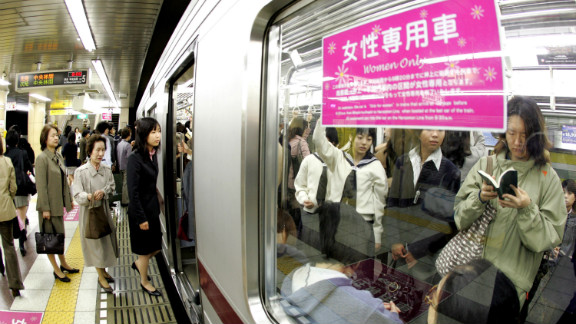"""Female passengers board a """"women-only"""" carriage at a metro station. Several private railways and subway trains operated by the Tokyo metropolitan government run the carriages during the morning rush hour in order to prevent """"chikan"""" (groping) in crowded trains."""
