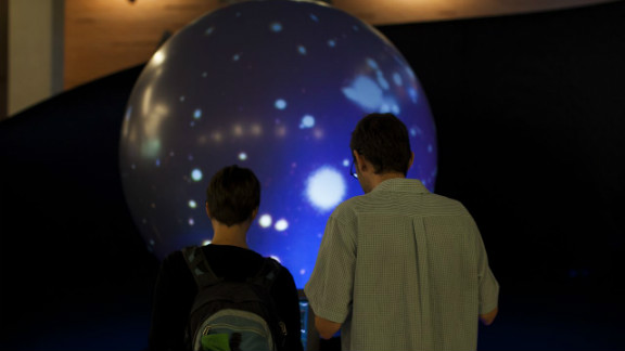 "Two sci-fi enthusiasts interact with an exhibit called the ""Magic Planet""at the Center for Science and the Imagination."