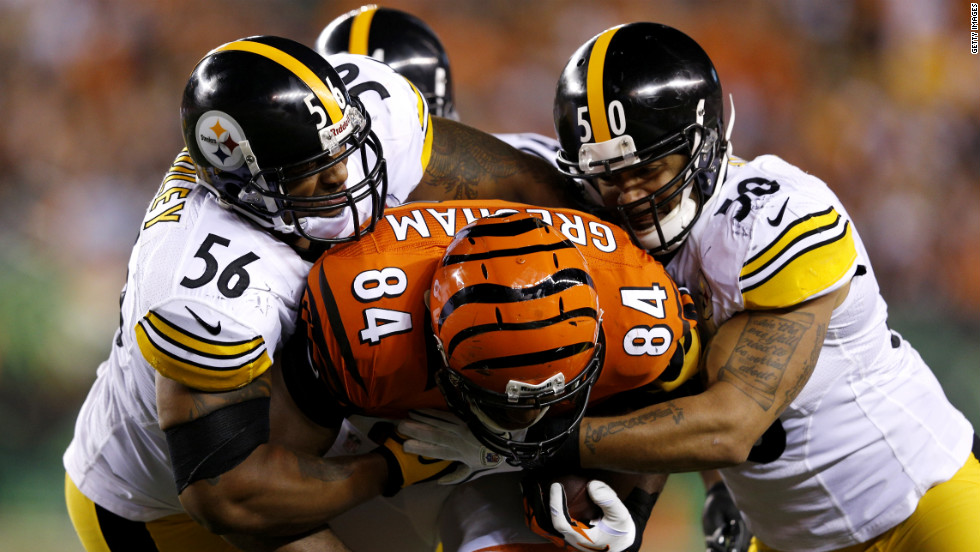 LaMarr Woodley, left, and Larry Foote of the Pittsburgh Steelers tackle Jermaine Gresham of the Cincinnati Bengals.