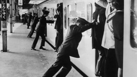 """""""Oshiya"""" (""""pushers"""") at Tokyo's Shinjuku station in the rush hour in 1967. They are employed to pack as many passengers as possible into the carriages. """"The peak rush hour is really unbelievable. I've only been a few times and I've really made an effort to avoid it ever since because it is really crowded. It's like a cattle cart,"""" says Barron."""