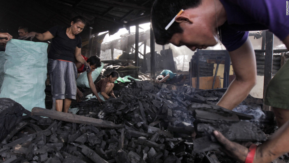 Residents of the slum of Tondo in Manila, Philippines, make charcoal by burning wood in shallow pits on Monday, October 22. Recent studies show that air pollution in Manila causes 60% of lung cancer cases, costing the country about $1.2 million in reduced productivity and another $21 million in health care.