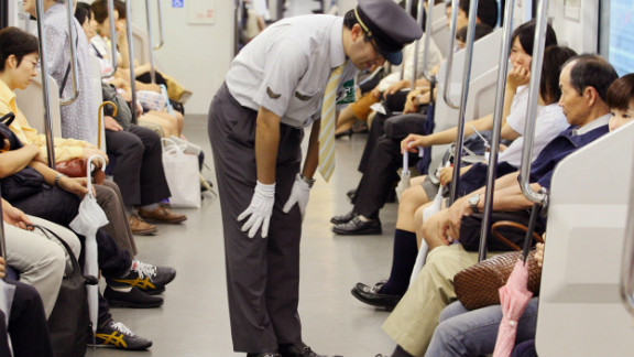 """A station staff member bows his head in front of passengers to apologize for delayed train at Japan Railway's station in Saitama city, northern Tokyo. The rail and subway network runs very smoothly, says Barron. """"Compared to New York, [Tokyo] is really efficient, really orderly, really clean ... """""""