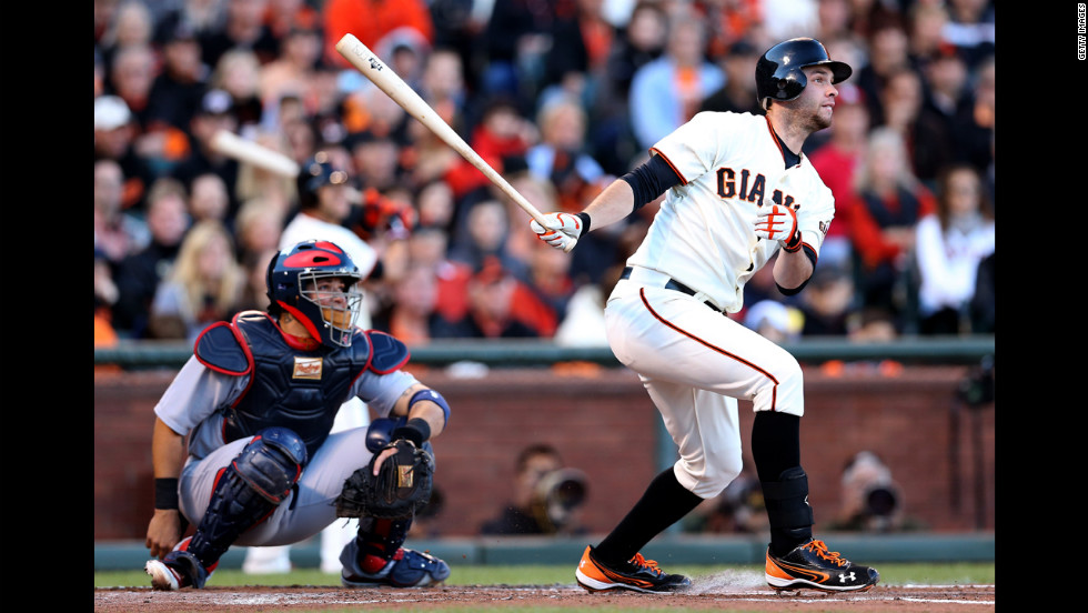 Brandon Belt of the San Francisco Giants hits a triple in the second inning against the St. Louis Cardinals.