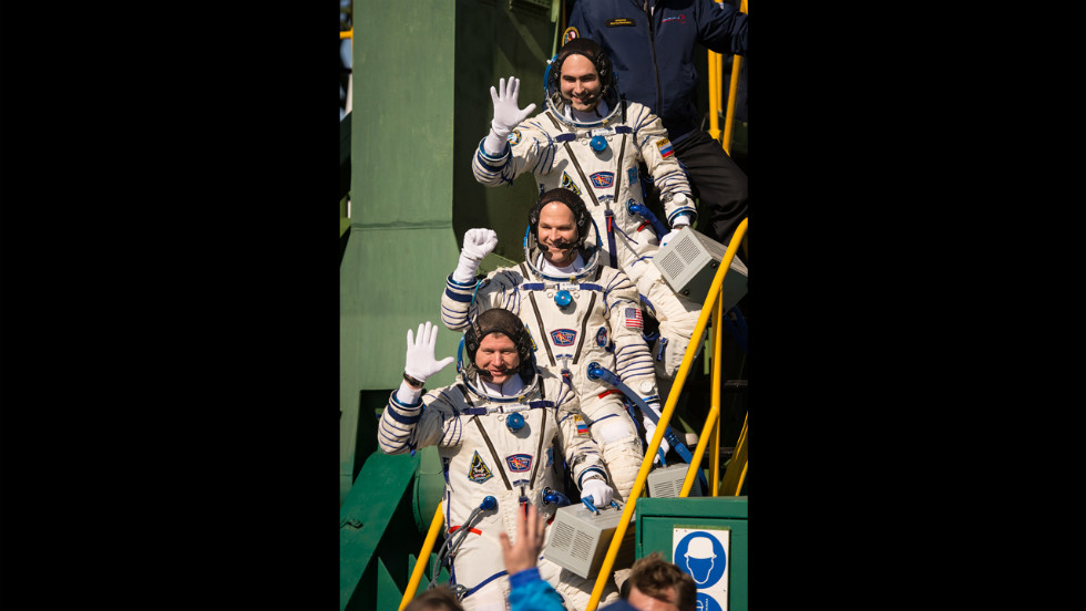 Flight engineer Evgeny Tarelkin, top, flight engineer Kevin Ford and Soyuz Cmdr. Oleg Novitskiy wave farewell before boarding the Soyuz spacecraft just a few hours before launch.